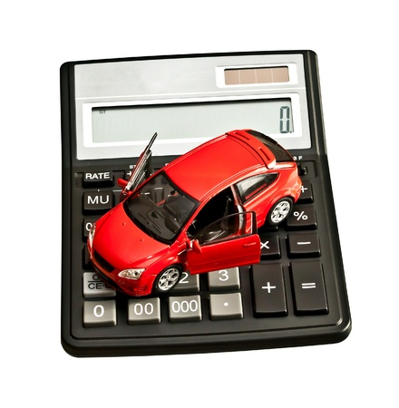 Toy car and calculator over white. Rent, buy, repair or insurance car concept photo
