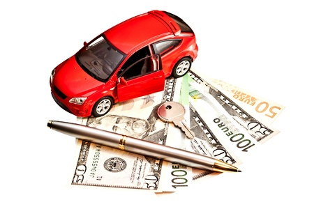 Toy car, key, pen and money over white  Rent, buy or insurance car concept photo