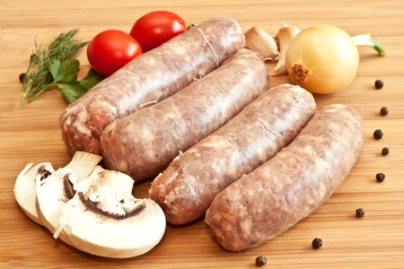 Uncooked sausages with vegetables on the chopping board Stock Photo
