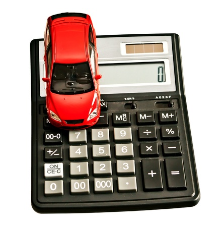 Toy car and calculator  Concept for buying, renting, insurance, fuel, service and repair costs photo