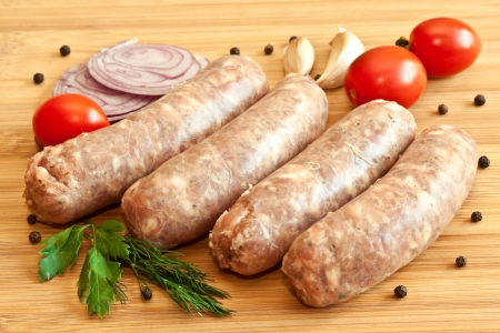 forcemeat: Uncooked sausages with vegetables on the chopping board Stock Photo