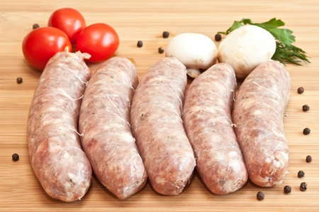 Uncooked sausage with vegetables on the chopping board photo