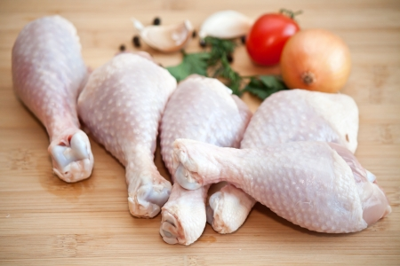Raw chicken legs with vegetables and spices on the chopping board Stock Photo - 22126226