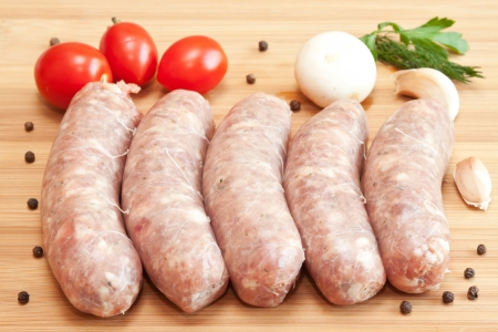 Uncooked sausages with vegetables on the chopping board  photo
