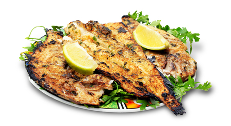 Grilled fish with greens on the plate - isolated on white background Stock Photo