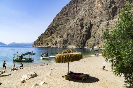 beach butterfly: Tourists visit famous Butterfly Valley beach near Oludeniz in Turkey Stock Photo