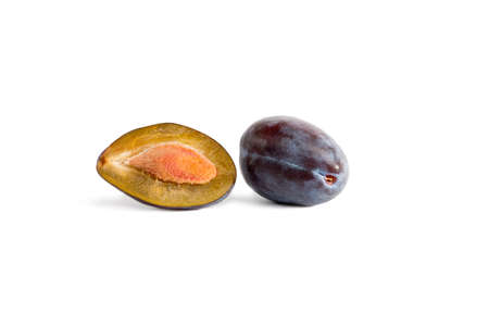 two and a half: two plums on a white background , one cut in half