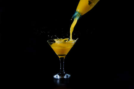 orange juice is poured from a bottle in a glass cup on a black background Stock Photo