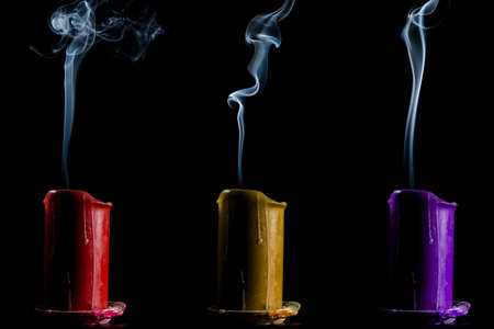 blow out: Candles red yellow and purple color faded on a dark background