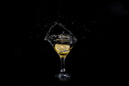 sweet vermouth: A slice of lemon dropped in a glass of cocktail. Spray fly on a dark background Stock Photo