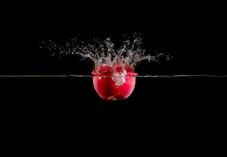 black red: red apple falls into water on dark background and takes up a lot of spray