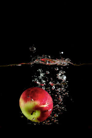 fell: red apple fell into the water and climb up many splashes on black background