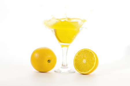 raises: lemon slice falls in a glass with a cocktail and raises a lot of splashes on white background