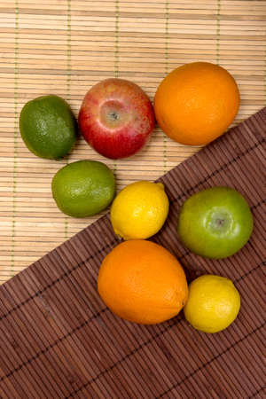 apple orange: lime, lemon, apple, orange lie on mats made of bamboo Stock Photo
