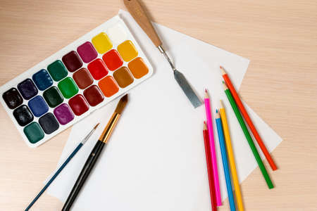 blank slate: paints and pencils for drawing are around a blank slate