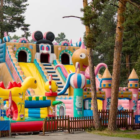 children celebration: childrens amusement park among trees inflatable city Stock Photo