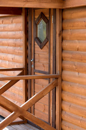 calibrated: Entrance door to a wooden house from a calibrated log