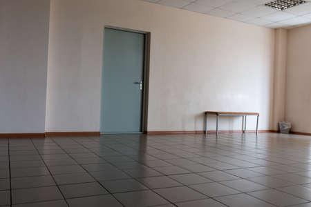 modern bathroom: Door on the wall in an office room tiled floor