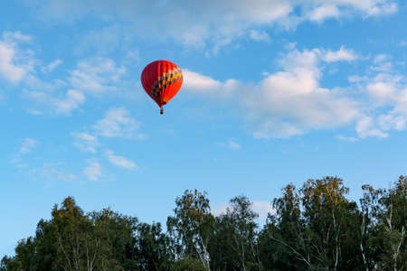 A balloon flies over the lake at sunset Stock Photo