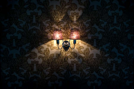 wall lamp glows on the wall with wallpaper