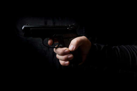 gun in the hand of man Stock Photo - 99156740