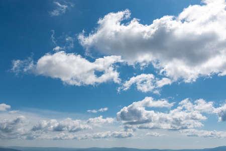 white fluffy clouds in bright blue sky
