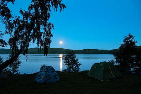 rest in a tourist tent on the shore of a picturesque lake on a summer day Stockfoto