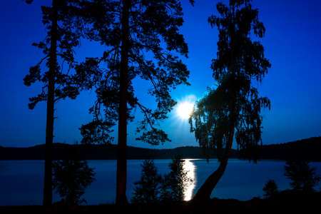 fantastic night landscape with moon over summer lake Stock Photo