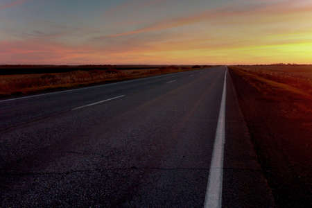 sunset road on a background of colorful sky i Stock Photo