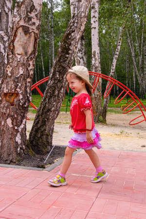 girl fun running around the playground in the summer