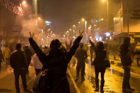 ISTANBUL, TURKEY - MARCH 11, 2014  A woman shows the victory sign in Kadikoy during protest after Berkin Elvan, who was 15 years old, died  He was hit in the head with a tear gas canister by Police  에디토리얼