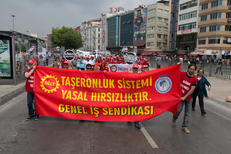 ISTANBUL, TURKEY - MAY 25, 2014: Unions march in protest against subcontractors in Turkey. Subcontracting system is legalized theft write on banner