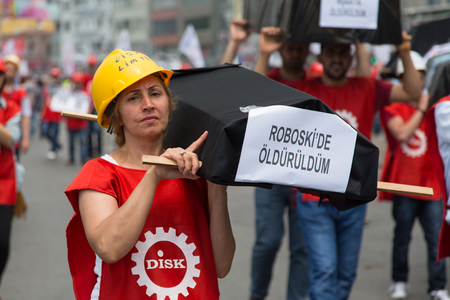 subcontractors: ISTANBUL, TURKEY - MAY 25, 2014: Woman with replica coffin in march in protest against subcontractors in Turkey. I dead in Roboski write on banner