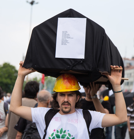 subcontractors: ISTANBUL, TURKEY - MAY 25, 2014: Man with replica coffin in march in protest against subcontractors in Turkey.