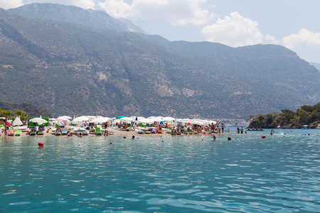 oludeniz: OLUDENIZ, MUGLA, TURKEY - JULY 19, 2014: People enjoying summer in Oludeniz beach. Oludeniz is one of the most famous beach in Turkey and also conjunction point of the Aegean and Mediterranean seas.