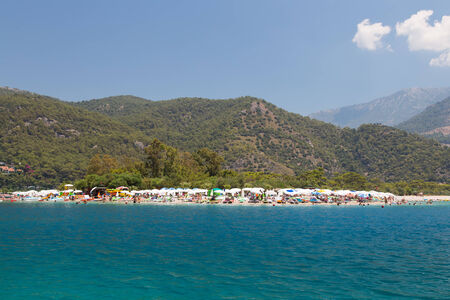 in conjunction: OLUDENIZ, MUGLA, TURKEY - JULY 19, 2014: People enjoying summer in Oludeniz beach. Oludeniz is one of the most famous beach in Turkey and also conjunction point of the Aegean and Mediterranean seas.