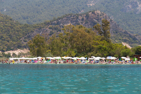 conjunction: OLUDENIZ, MUGLA, TURKEY - JULY 19, 2014: People enjoying summer in Oludeniz beach. Oludeniz is one of the most famous beach in Turkey and also conjunction point of the Aegean and Mediterranean seas.