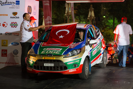 turkiye: ISTANBUL, TURKEY - AUGUST 15, 2014: Ferhat Tanribilir with Ford Fiesta R2 car of Castrol Ford Team Turkiye in ceremonial start of Avis Bosphorus Rally Editorial