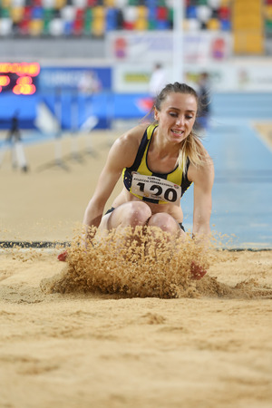 olympic game: ISTANBUL, TURKEY – JANUARY 17, 2015: Athlete Busra Mutay triple jump during Ruhi Sarialp clubs jumping championship and athletics record attempt races in Asli Cakir Alptekin Athletics hall