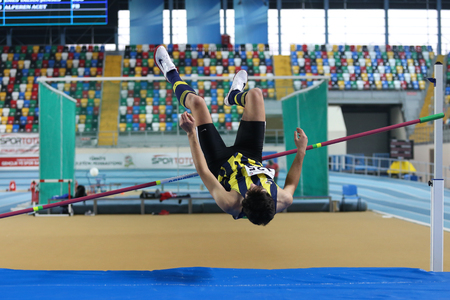 olympic game: ISTANBUL, TURKEY – JANUARY 17, 2015: Athlete Alperen Acet high jump during Ruhi Sarialp clubs jumping championship and athletics record attempt races in Asli Cakir Alptekin Athletics hall