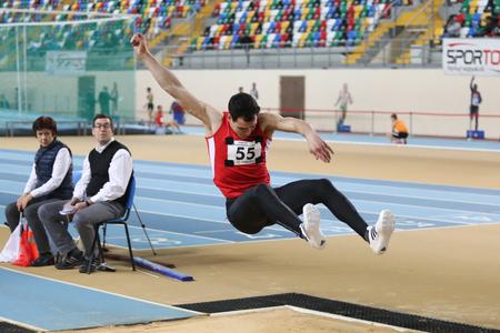 salto largo: ESTAMBUL, Turqu�a - 24 de enero 2015: El atleta Batuhan Altintas salto de longitud durante turca Federaci�n Atl�tica Competencia de Atletismo Indoor en el pabell�n Asli Cakir Alptekin Atletismo Editorial