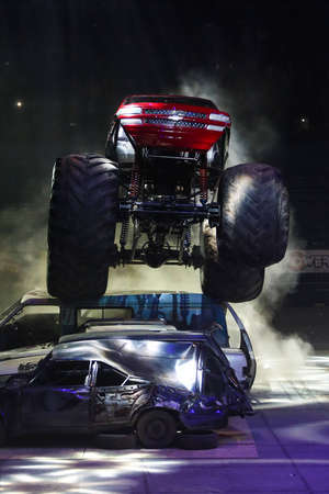 jalopy: ISTANBUL, TURKEY - JANUARY 31, 2015: Monster Truck Lil Devil crush to old cars in Sinan Erdem Dome during Monster Hot Wheels stunt show. Editorial