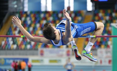 olympic game: ISTANBUL, TURKEY - FEBRUARY 21, 2015: Greek athlete Antonios Merlos high jump during Balkan Athletics Indoor Championships in Asli Cakir Alptekin Athletics hall.