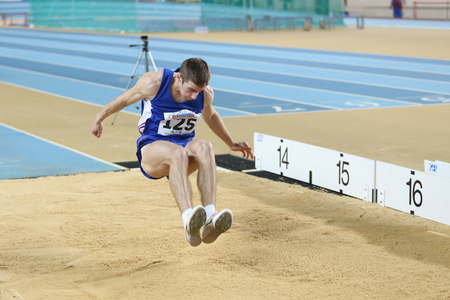 ISTANBUL, TURKEY - FEBRUARY 21, 2015: Armenian athlete Levon Aghasyan triple jump during Balkan Athletics Indoor Championships in Asli Cakir Alptekin Athletics hall. Редакционное