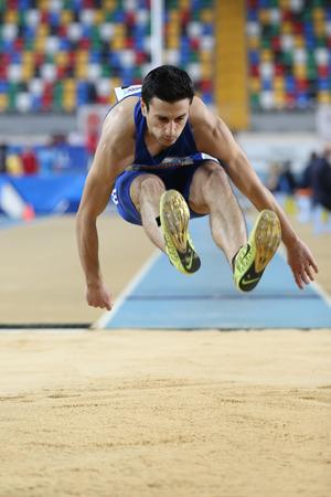 salto de longitud: ESTAMBUL, Turquía - 21 de febrero de 2015: atleta armenio Artak Hambardzumyan salto de longitud durante los Balcanes Atletismo Campeonatos de interior en el pabellón Asli Cakir Alptekin Atletismo. Editorial