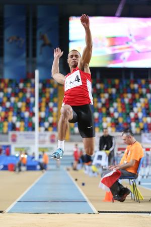 salto largo: ESTAMBUL, Turqu�a - 21 de febrero de 2015: atleta turca Seref Osmanoglu salto de longitud durante los Balcanes de Atletismo en pista cubierta en el pabell�n Asli Cakir Alptekin Atletismo.