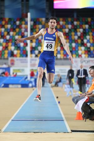 salto largo: ESTAMBUL, Turqu�a - 21 de febrero de 2015: atleta rumano Ionut Grecu salto de longitud durante los Balcanes de Atletismo en pista cubierta en el pabell�n Asli Cakir Alptekin Atletismo.