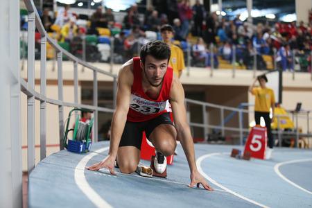 relay race: ISTANBUL, TURKEY - FEBRUARY 21, 2015: Turkish athlete Batuhan Altintas before 4x400 relay race during Balkan Athletics Indoor Championships in Asli Cakir Alptekin Athletics hall.