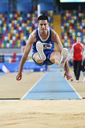 salto de longitud: ESTAMBUL, Turquía - 21 de febrero de 2015: atleta griego Michalis Mertzanidis salto de longitud durante los Balcanes Atletismo Campeonatos de interior en el pabellón Asli Cakir Alptekin Atletismo. Editorial