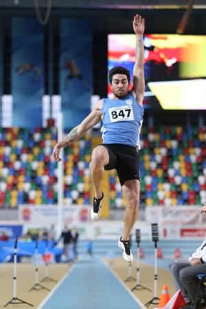 salto largo: ESTAMBUL, Turqu�a - 14 de febrero 2015: El atleta Volkan Cakan salto de longitud durante Turkcell Juniors y Seniors Atletismo Turqu�a Campeonato de interior en el pabell�n Asli Cakir Alptekin Atletismo